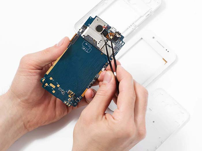 Repairman disassembling smartphone with tweezers. Unrecognizable repairer hands holding mobile phone circuit in electronics repair service, white background
